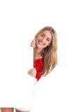 Pretty santa girl smiling at camera behind poster Royalty Free Stock Photos