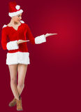 Pretty santa girl smiling at camera and presenting Royalty Free Stock Image