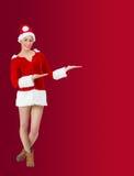 Pretty santa girl smiling at camera and presenting Stock Images