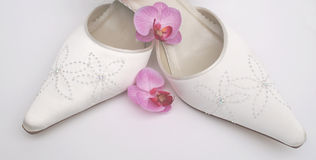 Pretty Satin Wedding Shoes. And delicate pink orchid blossom to represent a pretty bride Stock Photo