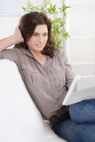 Pretty satisfied older woman at home - talking with tablet pc. Royalty Free Stock Photos