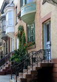 Pretty scene of row houses with colorful flowers in window boxes Stock Photos