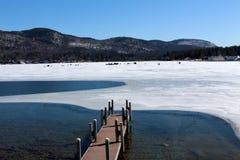 Ice fishing on lake with mountain range Royalty Free Stock Images