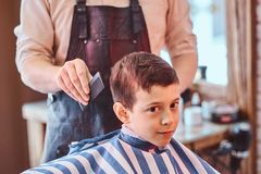 Pretty school boy had his first trendy haircut at modern barbershop. Small pretty school boy had his first trendy haircut at modern barbershop stock images