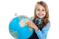 Pretty school child holding globe and pointing Stock Photo