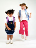 Pretty school girls jumping. Over white Royalty Free Stock Photography