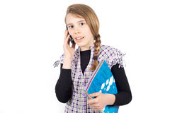 Pretty Schoolgirl With Books Talking on the Mobile Phone and Looking at Camera Royalty Free Stock Images