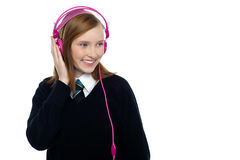 Pretty schoolgirl enjoying music Stock Image