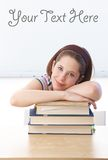 Pretty schoolgirl laying on books in classroom Royalty Free Stock Images