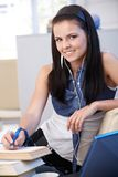 Pretty schoolgirl learning at home smiling Stock Image