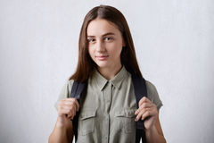 A pretty schoolgirl with long straight hair and dark beautiful eyes wearing elegant shirt holding rucksack on her back isolated ov stock images