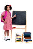 Pretty schoolgirl pointing at chalkboard Royalty Free Stock Photos