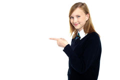 Pretty schoolgirl pointing towards copy space area Stock Images