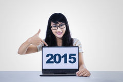 Pretty schoolgirl showing numbers 2015 on PC Royalty Free Stock Photography