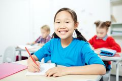 Individual drawing. Pretty schoolgirl with toothy smile looking at camera while sitting by individual seat at lesson royalty free stock photos