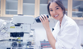 Pretty scientist smiling at the camera using microscope Royalty Free Stock Photography