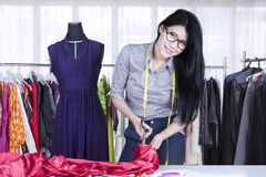 Pretty seamstress cutting a fabric in the workplace. Picture of a pretty seamstress cutting a fabric by using scissor while standing in the workplace Stock Image