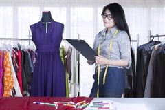 Pretty seamstress working with a clipboard. Image of pretty seamstress working with a clipboard while standing near a mannequin in the workplace Royalty Free Stock Images