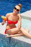 Pretty seated blonde in bikini with a drink Stock Photography