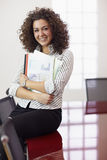 Pretty secretary with charts smiling at work Stock Photo