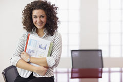 Pretty secretary with charts smiling at work Stock Image