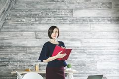 Pretty secretary concept. Portrait of attractive young woman with book, diary or notepad in office. Secretary concept Royalty Free Stock Images