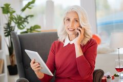 Pretty senior lady talking on smartphone at home. How are you. Beautiful retired woman listening to her friend talking on phone while sitting in a chair and Stock Photo