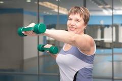 Pretty senior woman exercising in gym Stock Photos