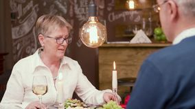 Pretty senior woman having a chat with her partner over a glass of wine stock video