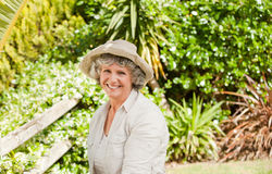 Pretty senior woman looking at the camera. In her garden Stock Photography