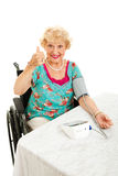 Thumbs Up for Low Blood Pressure. Pretty senior woman in wheelchair taking her blood pressure and giving thumbs up sign.  Isolated on white Stock Photos
