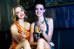 Pretty sensual girls in a nightclub, relishing wine. Glamorous girls enjoying wine at nightclub, legs crossed Stock Photos