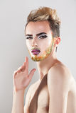 Pretty sensual man with makeup and multicolor beard looking at c. Amera. Studio shot. Vertical. Grey background Stock Photo