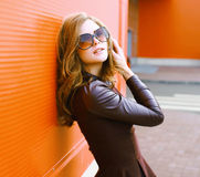 Pretty sensual woman in dress and sunglasses posing in the city Royalty Free Stock Photo