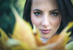 Pretty serene woman looking over autumn leaves Stock Photography