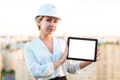 Pretty young forewoman in helmet stand on the roof and show empt. Pretty serious blonde caucasian forewoman in white building helmet, white blouse and black Royalty Free Stock Photo