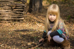 Pretty serious little blond girl playing outdoors Royalty Free Stock Photo