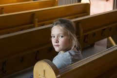 Pretty serious little girl sitting in church pew. With face turned to her left staring Royalty Free Stock Photo