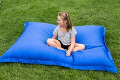 Little girl sitting cross-legged on giant blue exterior cushion. Pretty serious little girl in summer clothes sitting cross-legged on giant blue exterior cushion royalty free stock image