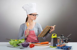 Pretty serious woman cooking with old cookbook Stock Photos