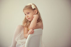 Pretty seriously ballet girl in white tutu sitting on chair Royalty Free Stock Image