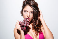 Pretty sexy brunette girl eating grapes wearing bikini Stock Photos