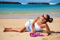 Pretty sexy brunette tanned woman lying on the exotic beach Royalty Free Stock Photography