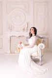 Pretty sexy brunette woman sitting on armchair Royalty Free Stock Images