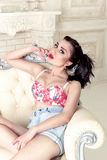 Pretty sexy brunette woman sitting on armchair Royalty Free Stock Photo