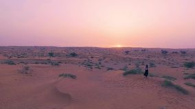 Pretty girl dances in desert with sun on background. Happy beautiful woman is dancing east dance on sand at sunset. Drone aerial shot. Slow motion stock video footage