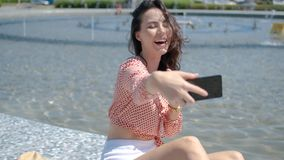 Pretty and sexy girl takin a selfie photo with her mobile phone. While sitting next to city fountain. Summer outdoor scenery stock video footage