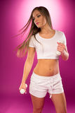 Pretty Sexy Lady Exercising Using Barbells. Pretty Sexy Lady Showing her Flat Stomach, Exercising Using Light Weight Barbells. Emphasizing Body Fitness Royalty Free Stock Photography