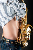 Pretty sexy sensual stomach of young blonde. With saxophone isolated over gray background Royalty Free Stock Image