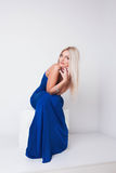 Pretty sexy woman with blonde hair in blue dress Stock Images
